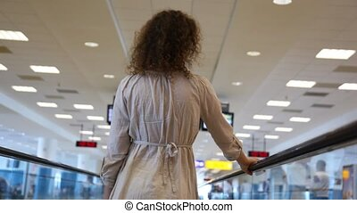 Woman moving on speedwalk and looks around at airport -...