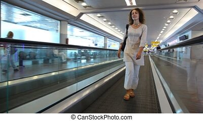 Woman walking on speedwalk at airport - Woman walking on...