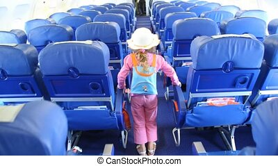 Little girl in pink suit and white hat walks in salon of Aeroflot airbus A320