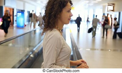 Woman moving on speedwalk at airport - Beautiful...