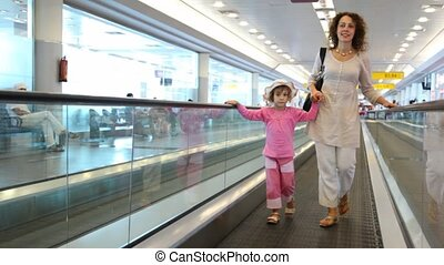 Woman and girl run on speedwalk at airport