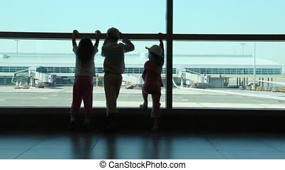 Silhouettes of children look through window of airport -...