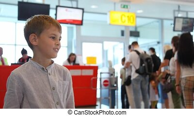 Boy talks to somebody near passport control at airport - boy...
