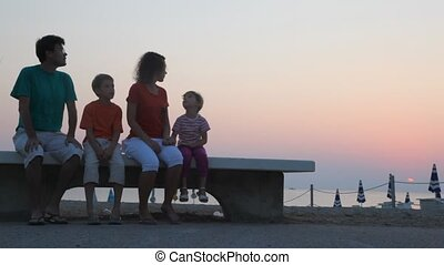 Parents and kids are sitting on bench and watching sunrise -...