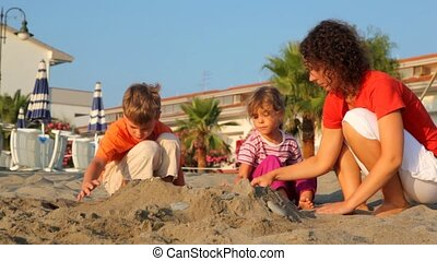 Mom and two kids are making sand pile