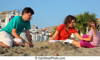 Father, mom and daughter, are playing sand at sunny day