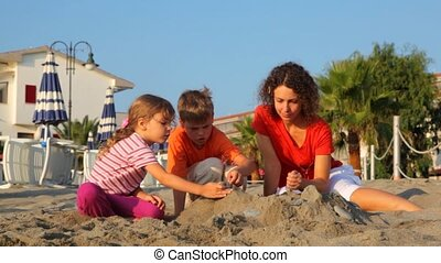 Mom and two kids are making sand pile - Mom and two kids,...