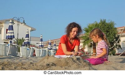 Mom and daughter are playing sand, they intersperse sand one...