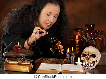Bewitched wine - Halloween witch putting a poisoned ring in...