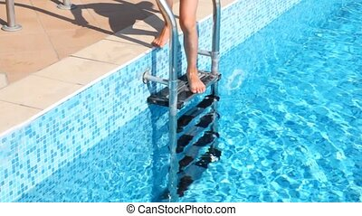 Boy in swimming cap descends in water in pool  by stair
