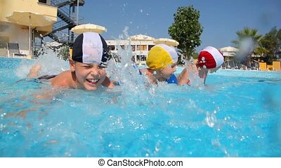 Boy and girls in swimming caps are splashing water - Boy and...