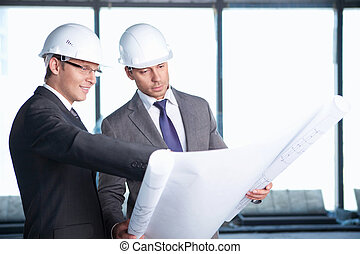 At construction site - Two men in hard hats at construction...