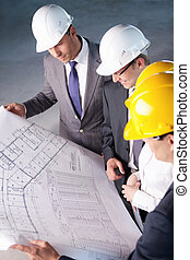 Planning - People in hard hats looking plan