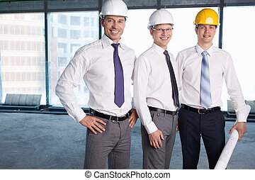 Construction - Business people in hard hats at construction...