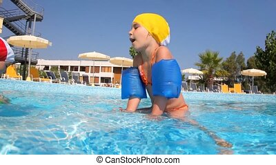 Girl slowly moving along the border in pool - Girl in...