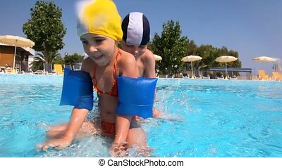 Girl and boy moving along the border in pool one by one -...