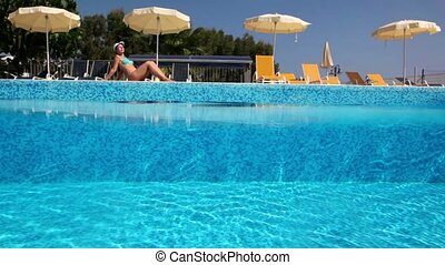 Woman tans near pool, camera is in water so water wave...