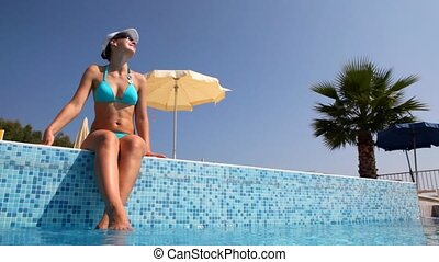Woman sits on pool border wets feet and tans, camera is on...
