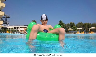 Boy sitting on inflatable chair in the pool water