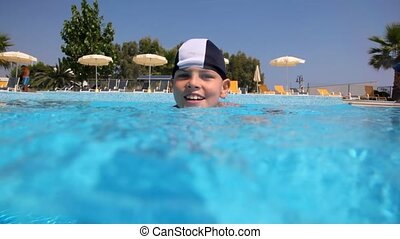 Boy in swimming cap in the pool water, the camera goes under...