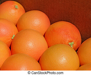 Pink grapefruits in cardboard box, shallow dof