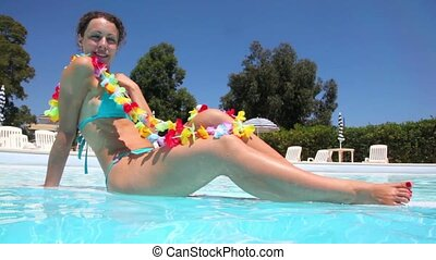 Woman in Hawaiian flowers sitting in the pool