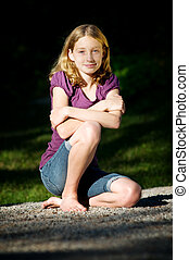 teen girl sitting outdoors - teen girl sitting on the ground...