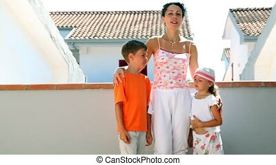 Mom and two kids are standing at balcony and mom speaking