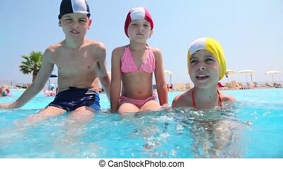 Boy and girls sitting in the pool, the boy splashes water -...