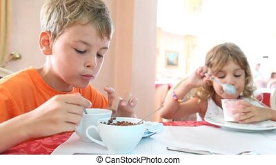 Boy and girl eat granola and yogurt for breakfast