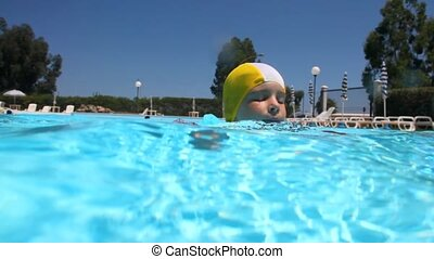 Little girl swimming in the pool, the camera takes a cart,...