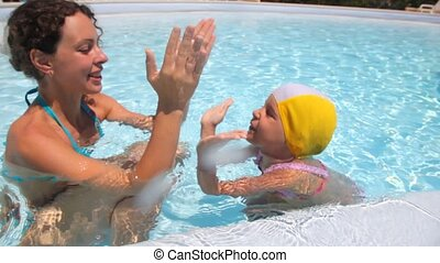 Mother and daughter are in the pool water playing palms