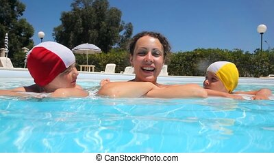 Woman and two girls are in the pool, looking and smiling