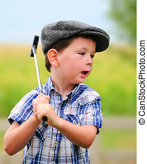 Litte boy golfer - Cute little boy in a driving hat playing...