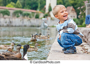 Cute little boy feeding ducks in the pond in a city park...