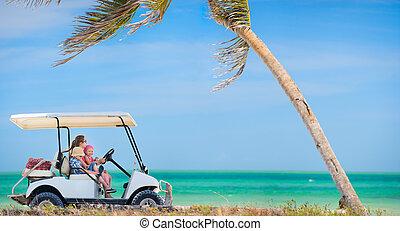 Golf cart at tropical beach - Family driving golf cart along...