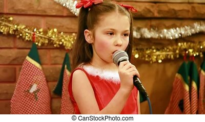 Girl sings Christmas song into microphone in front of...