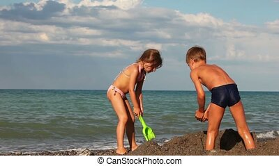 Boy and girl digging a hole in the sand, the boy took the...