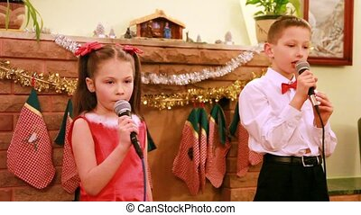 Sister and brother dance and sing song into microphone,...