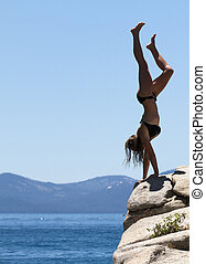 Teenager Handstand on a Rock Cliff - A teenage girl doing a...