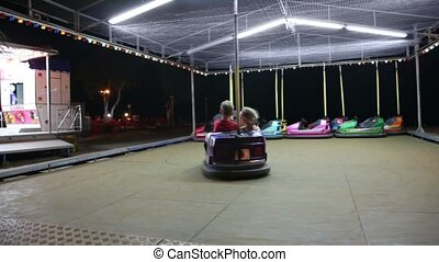 Two kids ride blue electric car - Two kids, boy and girl,...