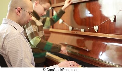 Father and son in glasses playing piano, concentrated faces