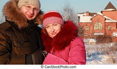 Woman and man at winter outdoors - young woman in pink...