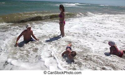 Parents and children wallowing in the sea waves rollsed -...