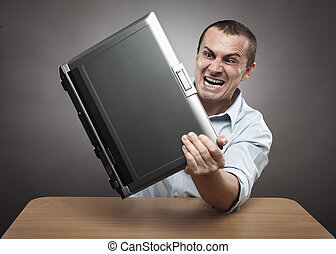 Angry businessman smashing his laptop - Extremely angry...
