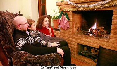 Father and son sitting in chair in front of fireplace, next to his mother