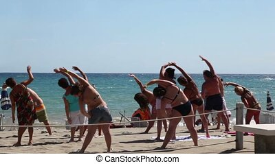 Tourists making aerobics on beach - CALABRIA, ITALY - JULY...