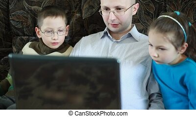 Father works on laptop sitting beside his son and daughter