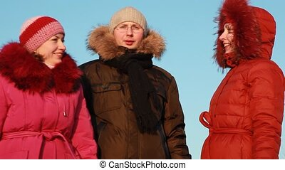 Man and two women standing outdoors at winter - Man in...