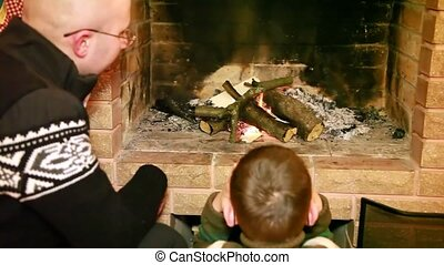 Father and son sitting by fireplace - Father and son wearing...